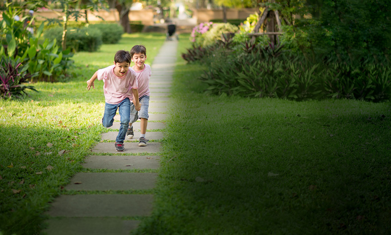 Two kids running through a neighborhood with smiles on their faces